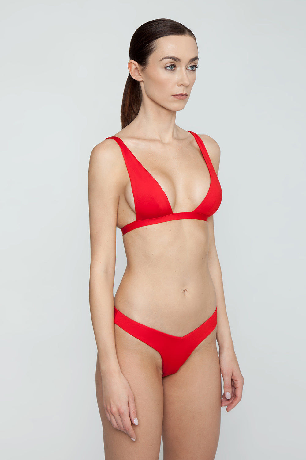 MONICA HANSEN BEACHWEAR Babe Watch V Bikini Bottom - Red Bikini Bottom | Red| Monica Hansen Beachwear Babe Watch V Bikini Bottom - Red Features:  Waist cut down in a V shape in front and in back Sides can be worn low rise or mid rise High cut leg  Cheeky coverage Italian fabric 85% Nylon 15% Elastane Manufactured in Italy Hand wash cold.  Dry Flat Side View