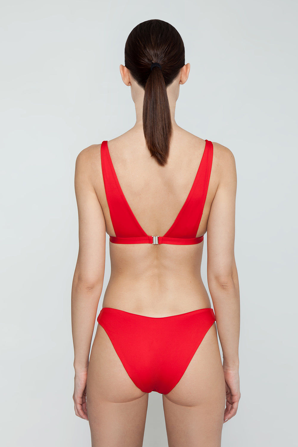 MONICA HANSEN BEACHWEAR Babe Watch V Bikini Bottom - Red Bikini Bottom | Red| Monica Hansen Beachwear Babe Watch V Bikini Bottom - Red Features:  Waist cut down in a V shape in front and in back Sides can be worn low rise or mid rise High cut leg  Cheeky coverage Italian fabric 85% Nylon 15% Elastane Manufactured in Italy Hand wash cold.  Dry Flat Back View