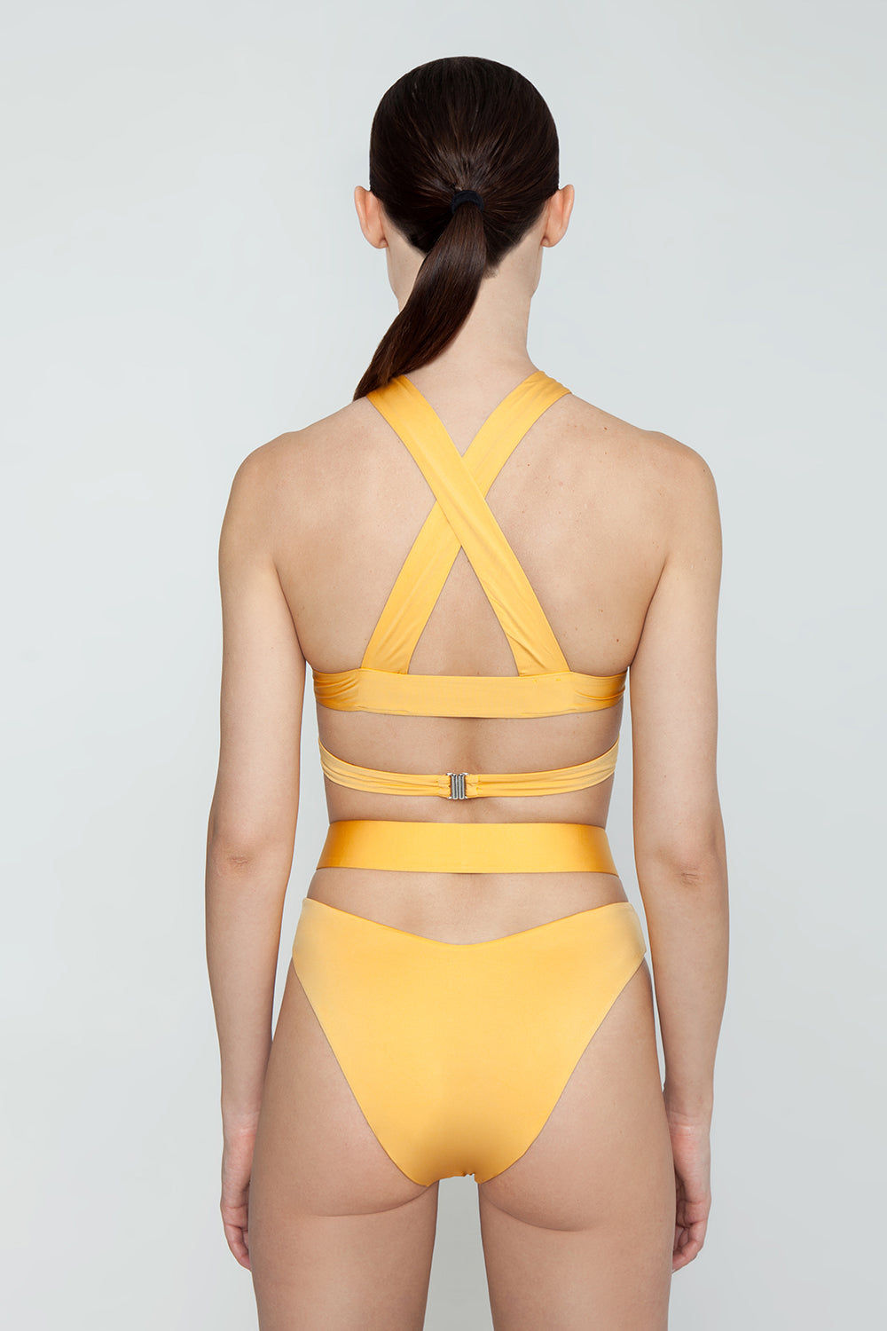 MONICA HANSEN BEACHWEAR Endless Summer Wrap Around Bikini Bottom - Honey Bikini Bottom | Honey| Monica Hansen Beachwear Endless Summer Wrap Around Bikini Bottom - Honey. Forms a diamond cut out in front Criss cross straps  High cut leg  Cheeky coverage  Double fabric on the inside instead of lining Italian fabric 85% Nylon 15% Elastane Manufactured in Italy Hand wash cold.  Dry Flat Back View