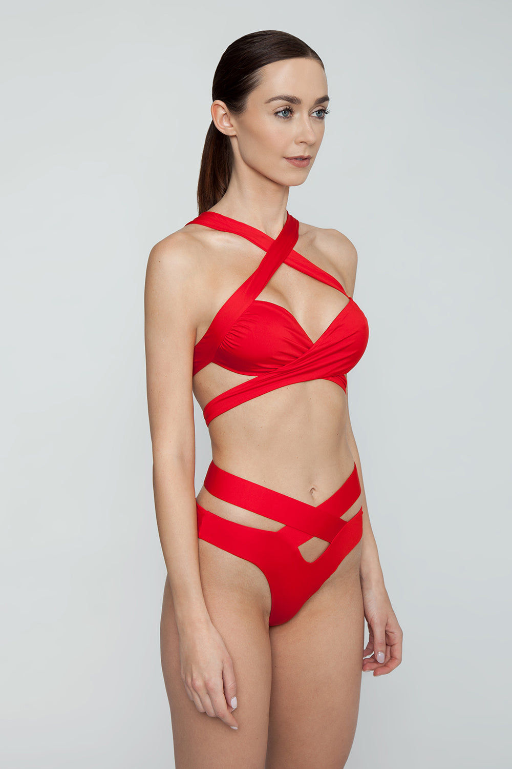 MONICA HANSEN BEACHWEAR Endless Summer Wrap Around Bikini Bottom - Red Bikini Bottom | Red| Monica Hansen Beachwear Endless Summer Wrap Around Bikini Bottom - Red. Forms a diamond cut out in front Criss cross straps  High cut leg  Cheeky coverage  Double fabric on the inside instead of lining Italian fabric 85% Nylon 15% Elastane Manufactured in Italy Hand wash cold.  Dry Flat Side View