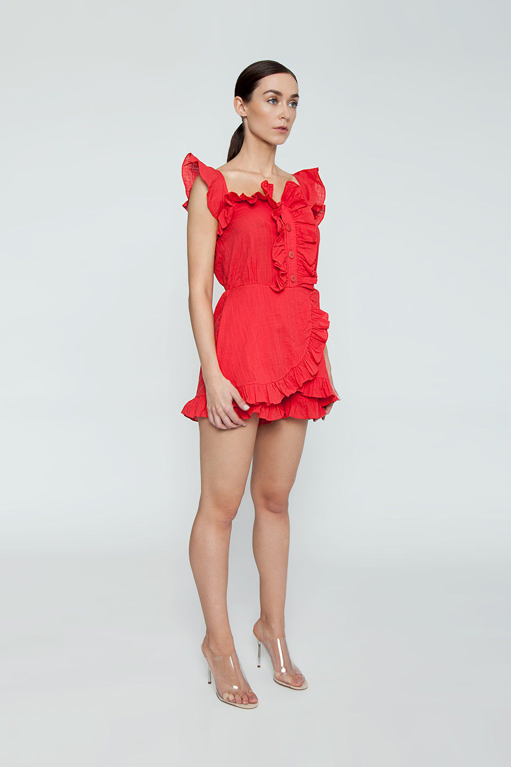 CLUBE BOSSA Follina Ruffle Romper - Pepper Red Romper | Pepper Red| Clube Bossa Follina Ruffle Romper - Pepper Red Ruffle romper Straight neckline  Ruffle sleeves Ruffle front detail  Front button closure  Side View
