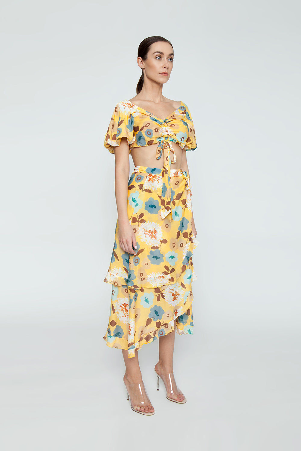 CLUBE BOSSA Sania Hi Lo Skirt - Cristal La Beija Floral Print Skirt | Cristal La Beija Floral Print| Clube Bossa Sania Hi Lo Skirt - Cristal La Beija Floral Print. Features:  High rise skirt Yellow floral print Mid-length Ruffle details Side View