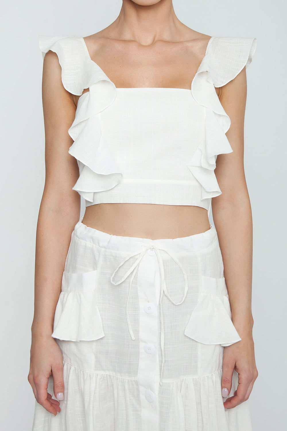 CLUBE BOSSA Lubba Cropped Blouse - Off White Top   Off White  Clube Bossa Lubba Cropped Blouse - Off White Features:  Square neckline Ruffle shoulders Back lace-up fastening 100% Cotton Detail View