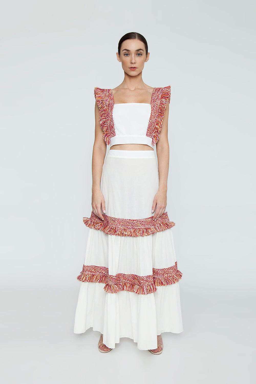 CLUBE BOSSA Pisan Long Fringe Skirt - White & Jazzy Fringes Red Skirt | White & Jazzy Fringes Red| Clube Bossa Pisan Long Fringe Skirt - White & Jazzy Fringes Red Long layered maxi skirt in white with warm-toned fringe tier detail. The bold red and yellow toned fringe pops off the contrasting clean white of this skirt. The high waisted Front View