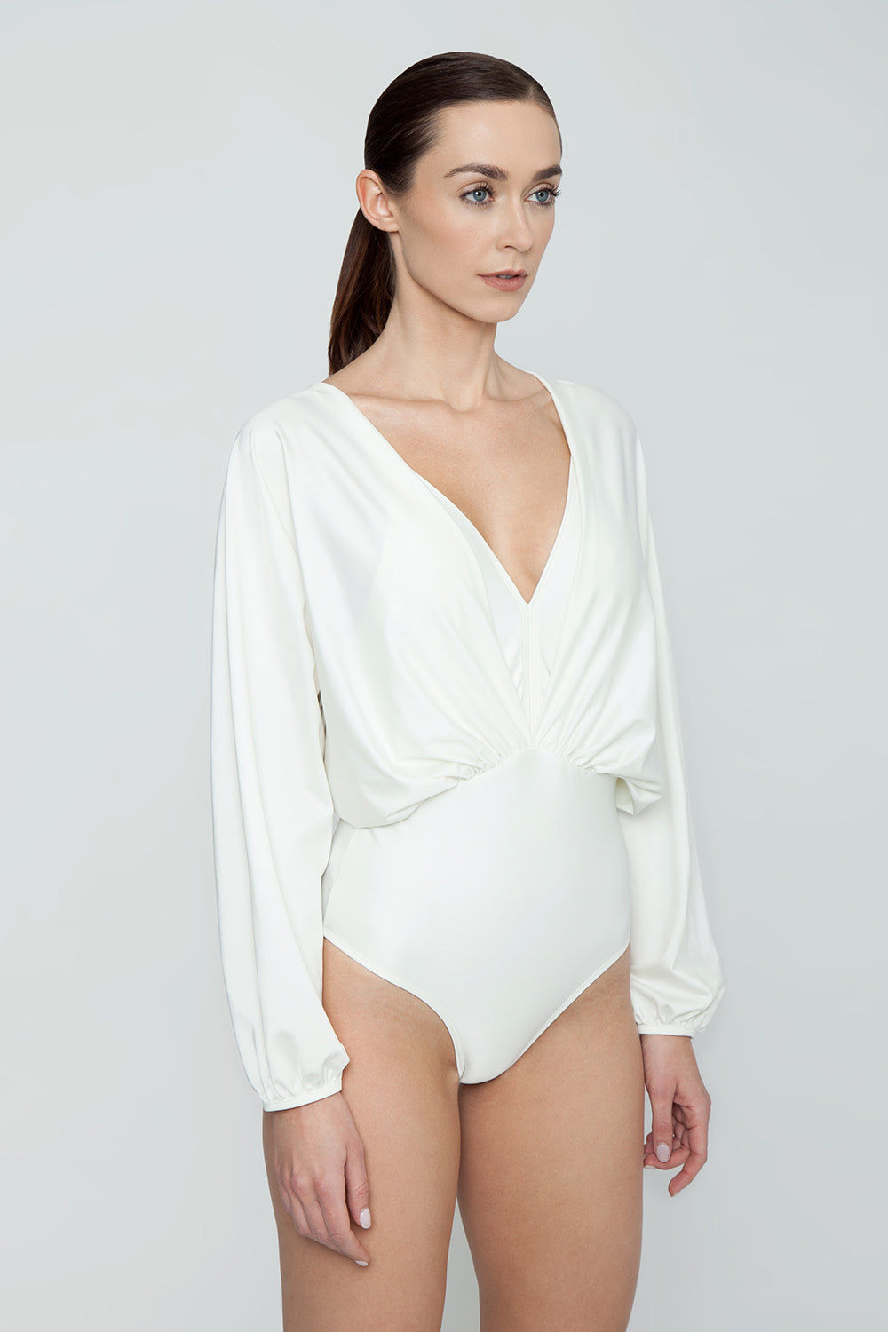 AGUA DE COCO Brazilian Long Sleeves One Piece Swimsuit - Off White One Piece | Off White| Agua De Coco Brazilian Long Sleeves One Piece Swimsuit - Off White White one piece Plunging v neckline Gathered fabric  Long sleeves  Open back detail  Cheeky - moderate coverage Side View