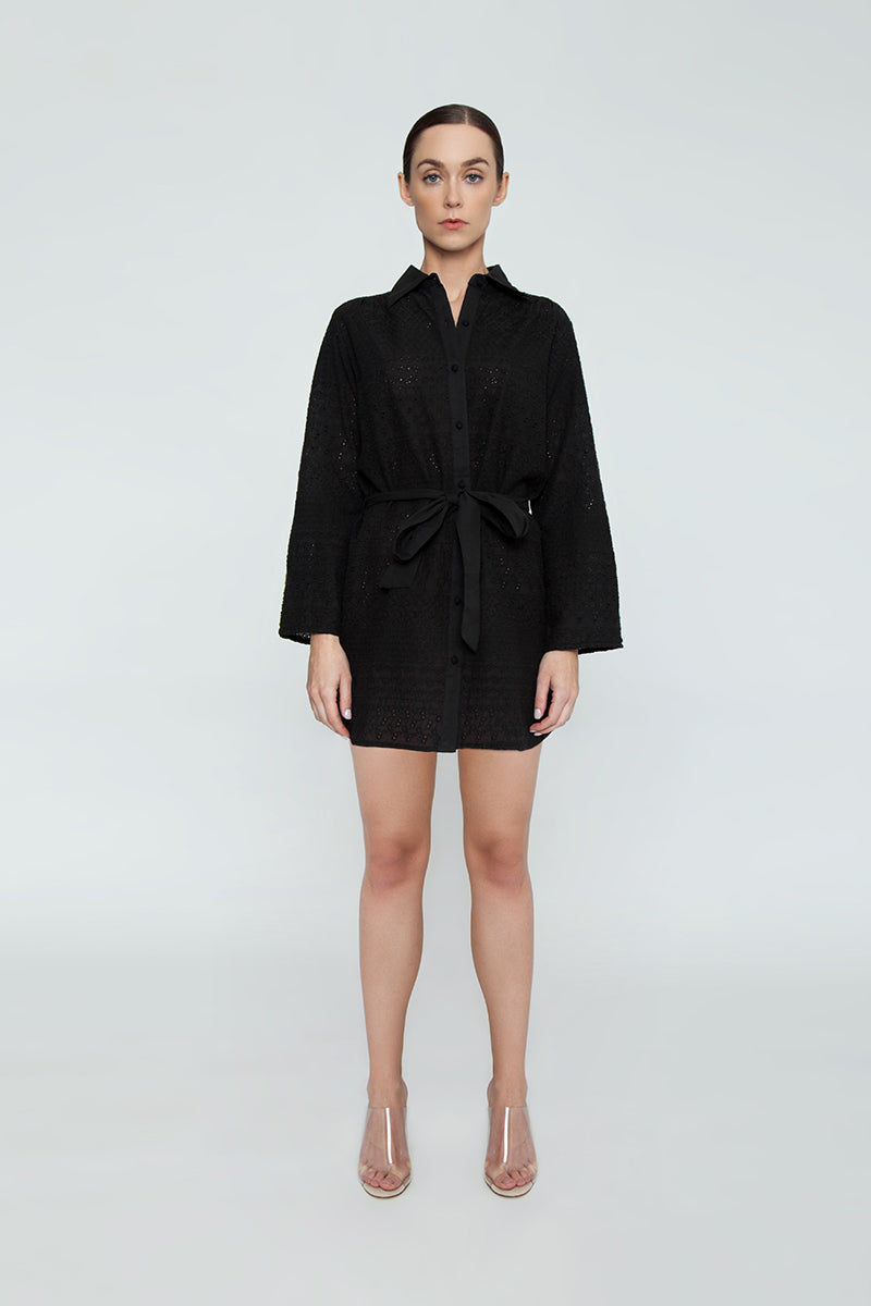 "AMITA NAITHANI Signature Eyelet Big Shirt Dress - Black Dress | Black| Amita Naithani Signature Eyelet Big Shirt Dress - Black. Features:  All Over Stripe Eyelet Button Front w/ Spread Collar  Pocket w/ Side Slit Dolphin Hem About 32"" from hips to hem  Imported 100% Cotton Machine Wash Front View"