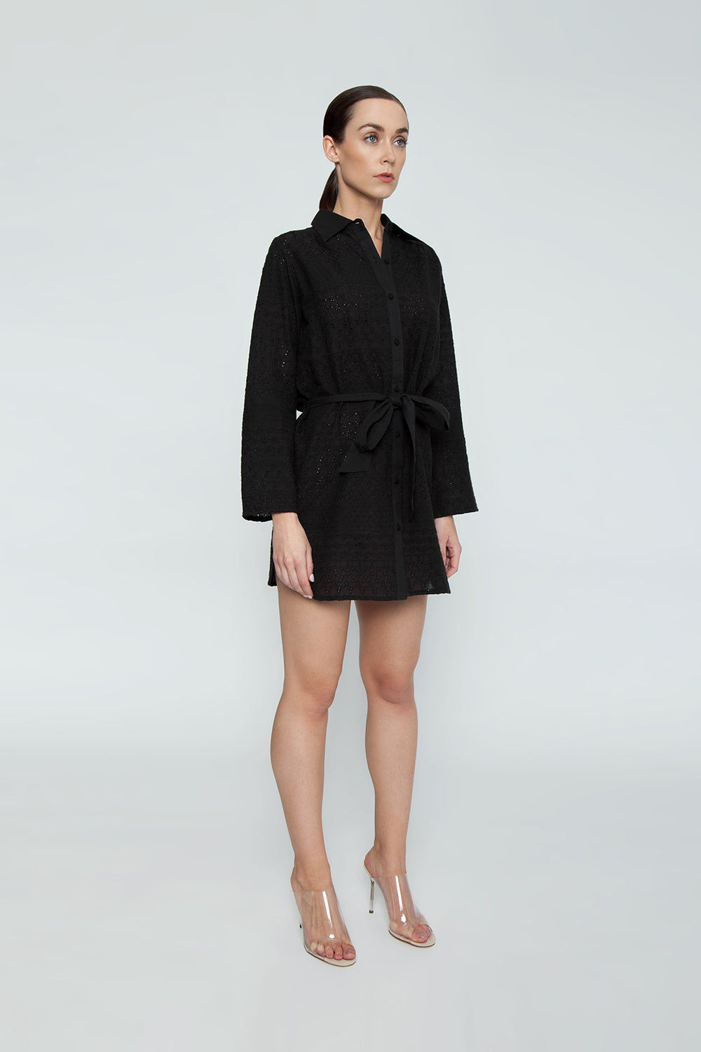 "AMITA NAITHANI Signature Eyelet Big Shirt Dress - Black Dress | Black| Amita Naithani Signature Eyelet Big Shirt Dress - Black. Features:  All Over Stripe Eyelet Button Front w/ Spread Collar  Pocket w/ Side Slit Dolphin Hem About 32"" from hips to hem  Imported 100% Cotton Machine Wash Side View"