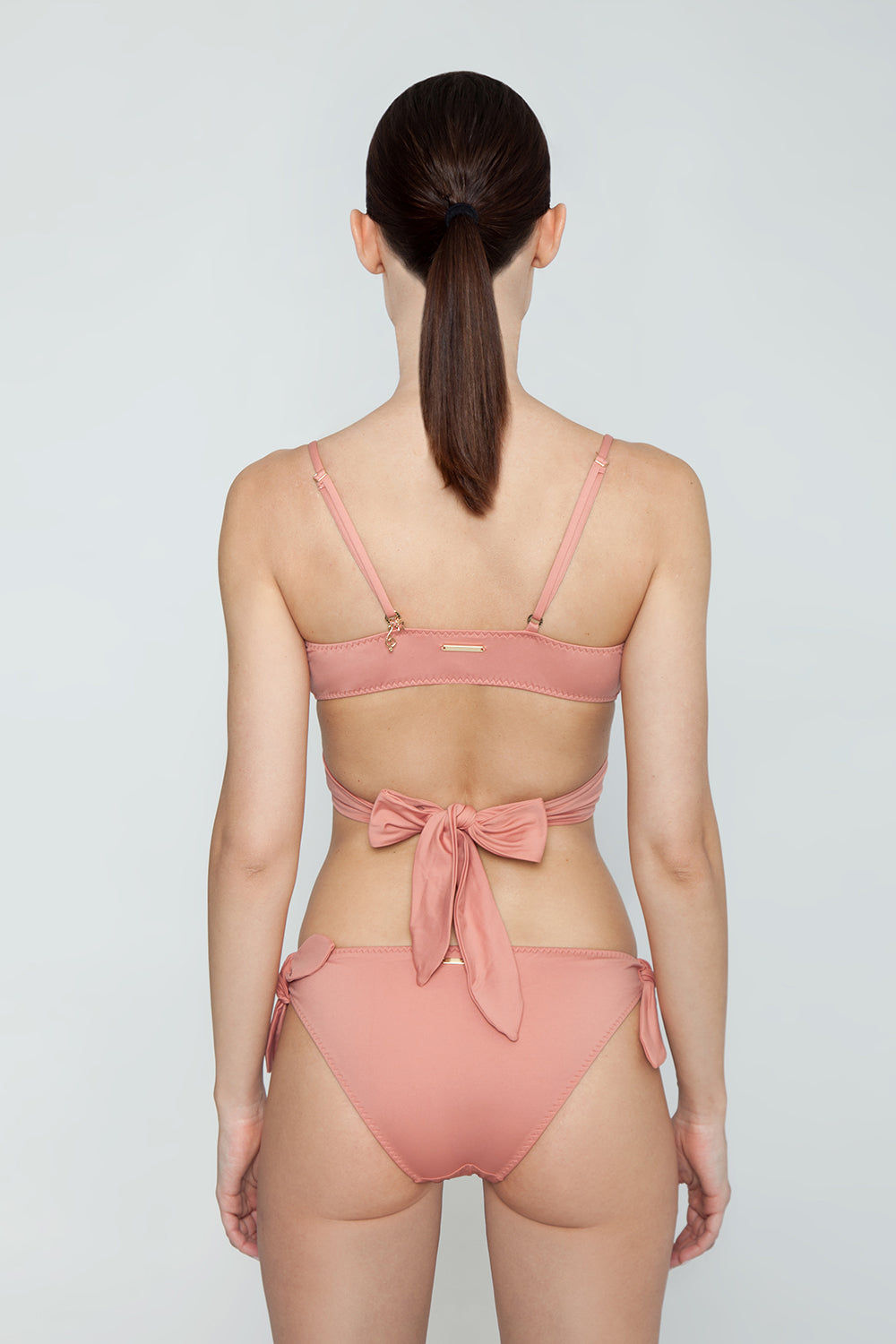 STELLA MCCARTNEY Wrap Bikini Top - Antique Rose Pink Bikini Top | Antique Rose Pink| Stella McCartney Wrap Bikini Top - Antique Rose Pink Figure-flattering true wrap bikini top in pretty dusty rose color. Soft unpadded triangle cups criss-cross below bust and tie at mid-back in a chunky feminine bow. Boned sides with slight ruching detail subtly sculpt and flatter the bust without the need for padding or underwire. Back View