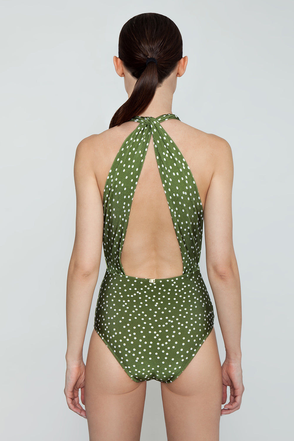 ADRIANA DEGREAS Plunging Halter Neck One Piece Swimsuit - Mille Punti Army Green Polka Dot Print One Piece | Mille Punti Army Green Polka Dot Print| ADRIANA DEGREAS Plunging Halter Neck One Piece Swimsuit - Mille Punti Army Green Polka Dot Print Plunging halter neck one piece swimsuit in army green polka dot print. Inspired by 1950s pin-up style, the halter neckline features flattering pleats and extra coverage at underarms. Fixed halter strap connects behind neck to wide draped straps Back View