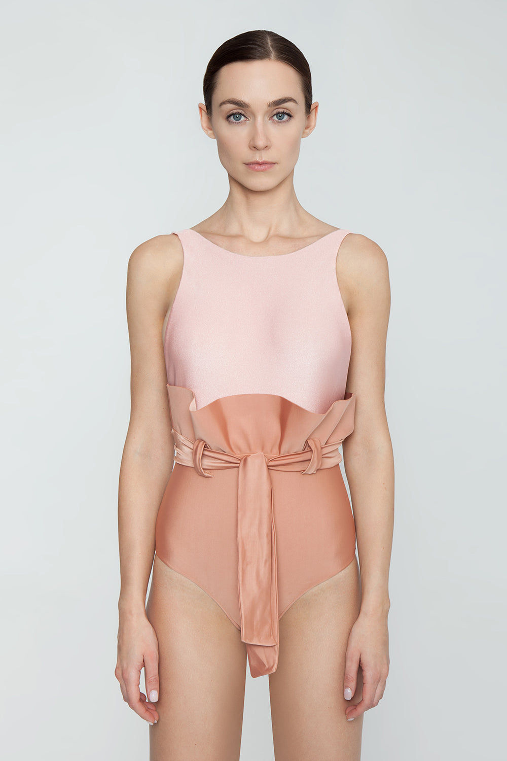 ADRIANA DEGREAS Clochard Ruffle Waist Tie One Piece Swimsuit - Bicolor Light Pink/Rose Pink One Piece | Bicolor Light Pink/Rose Pink| Adriana Degreas Bicolor Clochard One Piece Swimsuit - Light Pink/Rose Pink Features:  Slight scoop neckline Thick back straps Ruffle detail  Self tie waist  Moderate coverage  Front View