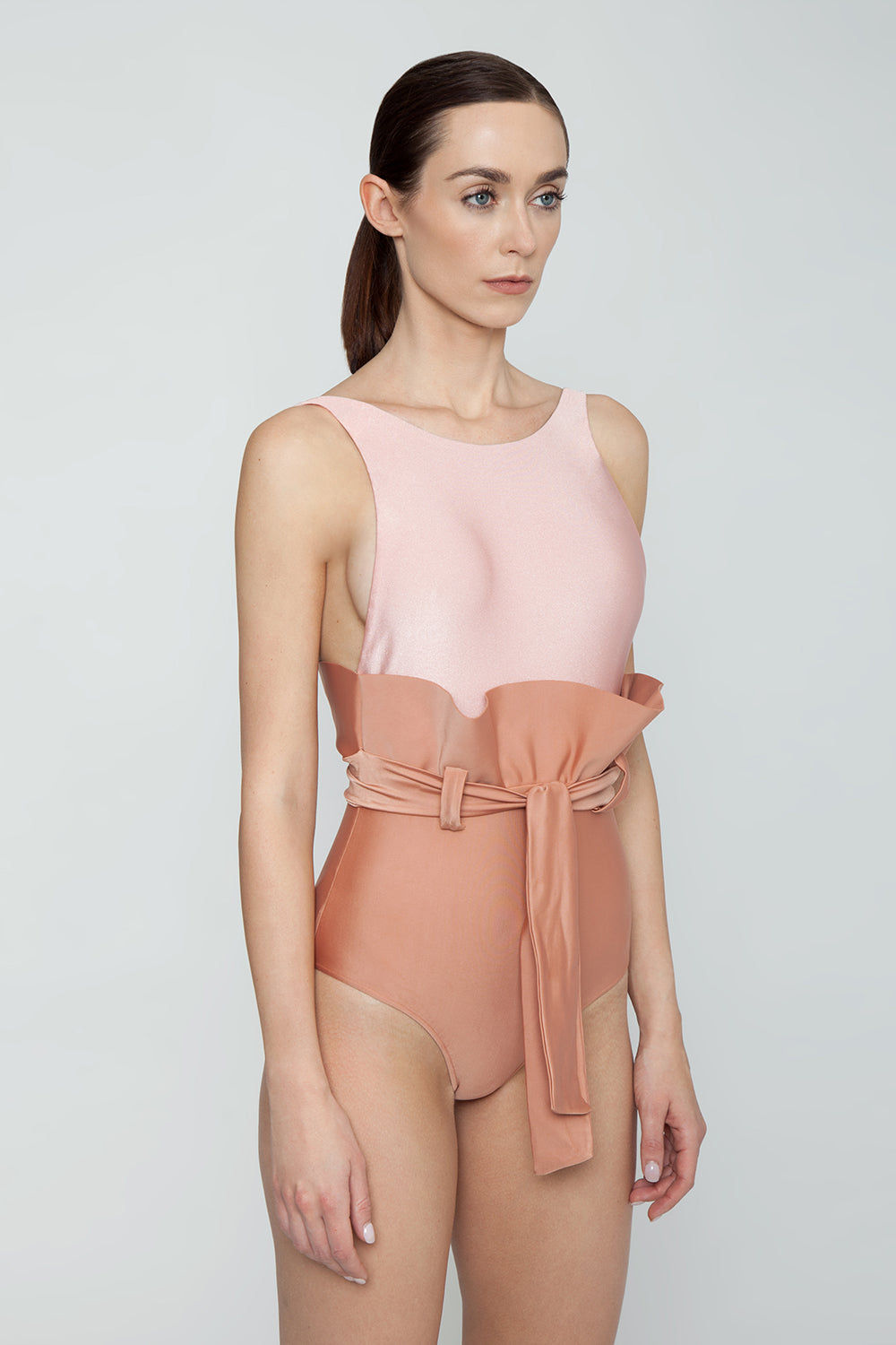 ADRIANA DEGREAS Clochard Ruffle Waist Tie One Piece Swimsuit - Bicolor Light Pink/Rose Pink One Piece | Bicolor Light Pink/Rose Pink| Adriana Degreas Bicolor Clochard One Piece Swimsuit - Light Pink/Rose Pink Features:  Slight scoop neckline Thick back straps Ruffle detail  Self tie waist  Moderate coverage  Side View