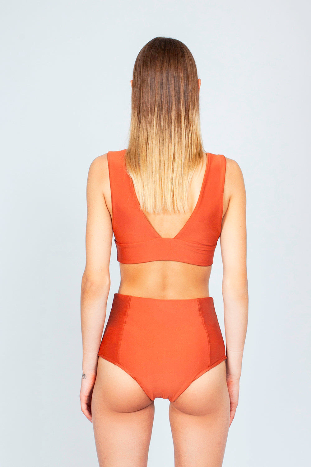 THE ONES WHO Dive Long Triangle Bikini Top - Copper Orange Bikini Top   Copper Orange  The Ones Who Dive Long Triangle Bikini Top - Copper Orange Long triangle top  V neckline  Thick bra band  V Back  Pull over  Made in LA  Fabric: 80% Nylon 20% Elastane Back View