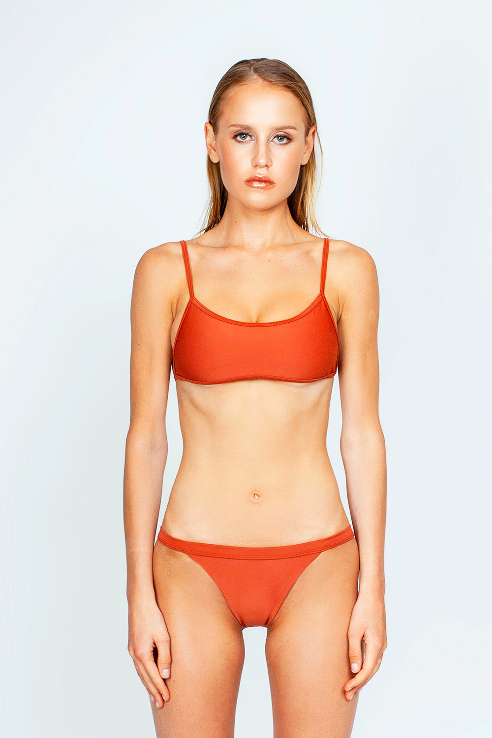 THE ONES WHO Ava Sporty Bikini Top - Copper Orange Bikini Top | Copper Orange| The Ones Who Ava Sporty Bikini Top - Copper Orange Sporty and minimal top Adjustable shoulder straps Self-tie back Fully lined with no cups Made in LA  Fabric: 80% Nylon 20% Elastane Front View