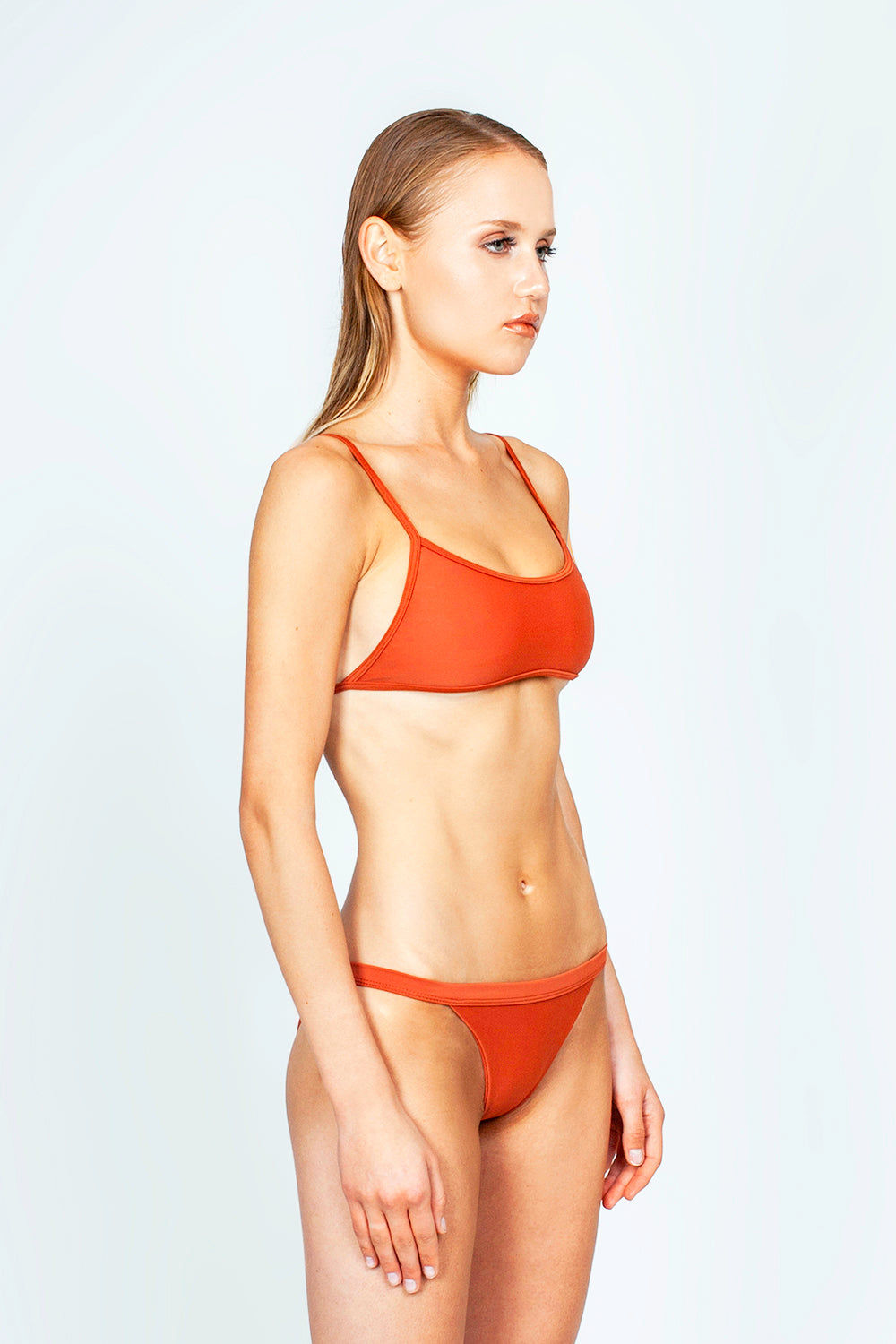 THE ONES WHO Ava Sporty Bikini Top - Copper Orange Bikini Top | Copper Orange| The Ones Who Ava Sporty Bikini Top - Copper Orange Sporty and minimal top Adjustable shoulder straps Self-tie back Fully lined with no cups Made in LA  Fabric: 80% Nylon 20% Elastane Side View