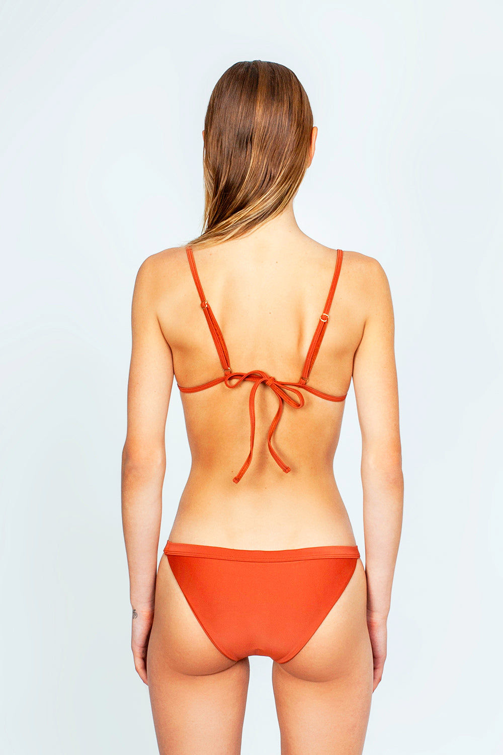 THE ONES WHO Ava Sporty Bikini Top - Copper Orange Bikini Top | Copper Orange| The Ones Who Ava Sporty Bikini Top - Copper Orange Sporty and minimal top Adjustable shoulder straps Self-tie back Fully lined with no cups Made in LA  Fabric: 80% Nylon 20% Elastane Back View