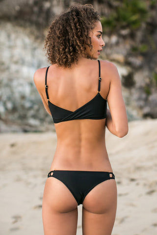 ISSA DE' MAR Hina Side Cut Out Cheeky Bikini Bottom - Black Bikini Bottom | Black| Issa De' Mar Hina Side Cut Out Cheeky Bikini Bottom - Black Cheeky coverage bikini bottom in a classic black is a summer swim wardrobe staple that shows off your best assets. Seamless and hardware-free, this bikini bottom is perfect for all-day, fuss-free wear. Wide side straps hug your curves while peek-a-boo caged cut-outs Back View