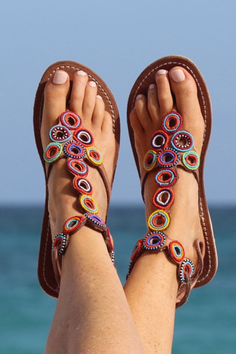 ASPIGA Kalifi Sandals - Multicolor Sandals | Multicolor| Aspiga Kalifi Sandals - Multicolor Flip flop style Unusual hand beaded circle detailing Fasten with genuine leather laces Flat flexible sole  Genuine tan leather upper Hand crafted in Kenya On Model View
