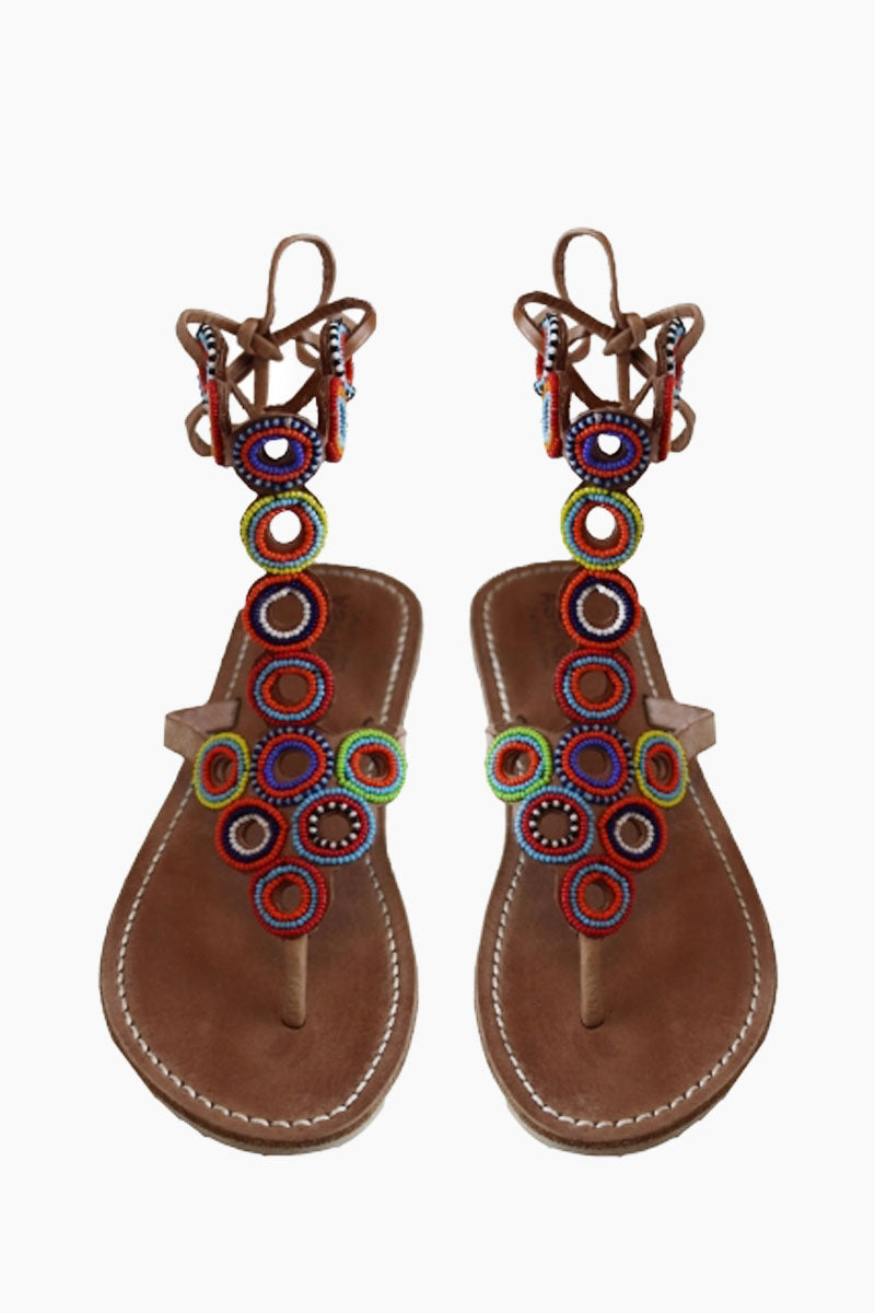 ASPIGA Kalifi Sandals - Multicolor Sandals | Multicolor| Aspiga Kalifi Sandals - Multicolor Flip flop style Unusual hand beaded circle detailing Fasten with genuine leather laces Flat flexible sole  Genuine tan leather upper Hand crafted in Kenya Front View