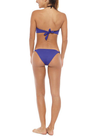 KORE Phoebe Double Side Strap Bikini Bottom - Ultraviolet Blue Bikini Bottom | Ultraviolet Blue| KORE Phoebe Double Side Strap Bikini Bottom - Ultraviolet Blue Low-rise double side strap cheeky bikini bottom in indigo blue. The low-rise cut and overall skimpy coverage give this bikini bottom the perfect tanning silhouette. Double side straps stay secure while swimming and expose skin through small cut-outs. Moderate rear cut shows off your curves while providing cheeky coverage. Back View