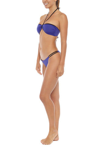 KORE Phoebe Double Side Strap Bikini Bottom - Ultraviolet Blue Bikini Bottom | Ultraviolet Blue| KORE Phoebe Double Side Strap Bikini Bottom - Ultraviolet Blue Low-rise double side strap cheeky bikini bottom in indigo blue. The low-rise cut and overall skimpy coverage give this bikini bottom the perfect tanning silhouette. Double side straps stay secure while swimming and expose skin through small cut-outs. Moderate rear cut shows off your curves while providing cheeky coverage. Front View