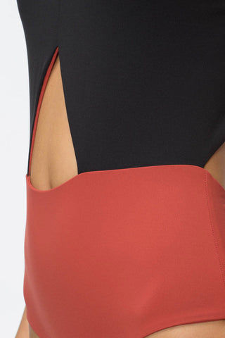 TAVIK Lela High Neck Cut Out One Piece Swimsuit - Rust Red/Black One Piece | Rust Red/Black|TAVIK Lela High Neck Cut Out One Piece Swimsuit - Rust Red/Black High neck cutout one-piece swimsuit in rust color block. Narrow high neckline frames your face while the ultra-thin white shoulder straps crisscross at the back and are adjustable to your fit. Mid to low cut leg with a cheeky backside coverage give this one piece a classic sporty look Front View
