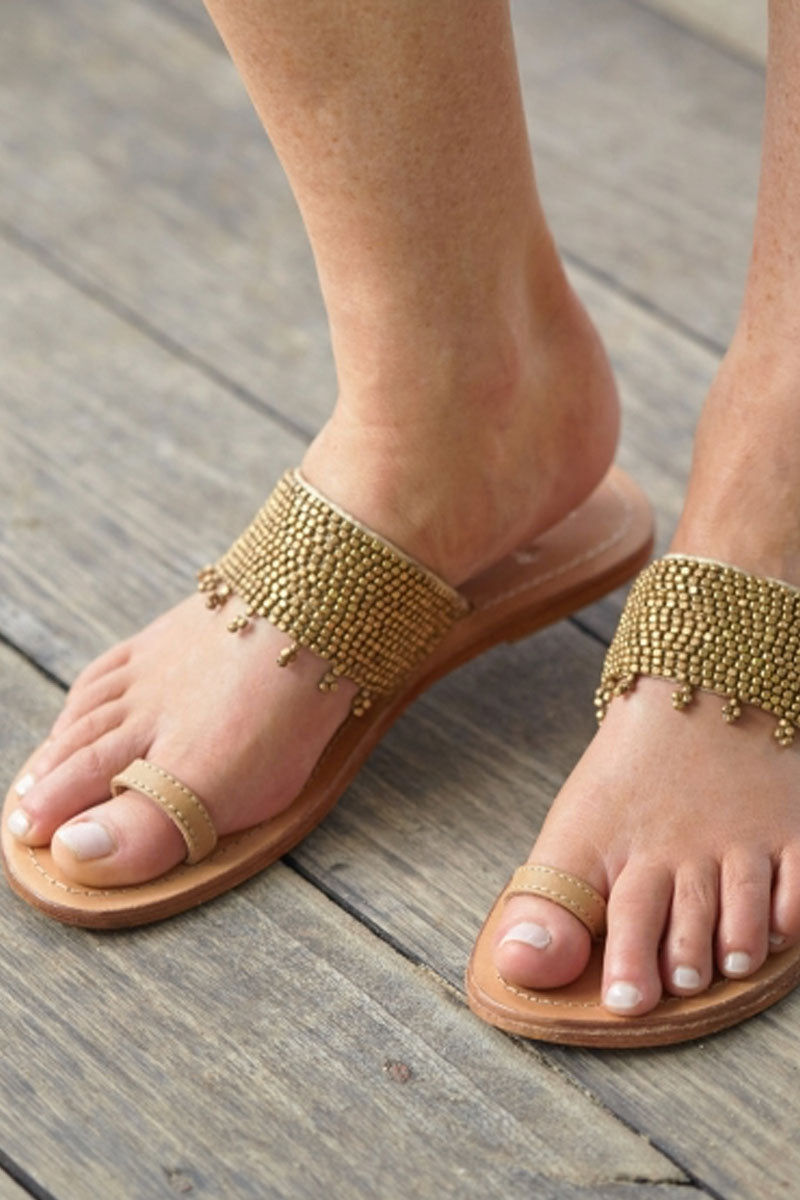 ASPIGA Luna Sandals - Gold Sandals | Gold| Aspiga Luna Sandals - Gold Toe loop style Over the foot strap embellished metal beading  Flat flexible rubber sole Genuine tan leather Hand crafted in Kenya on Model View