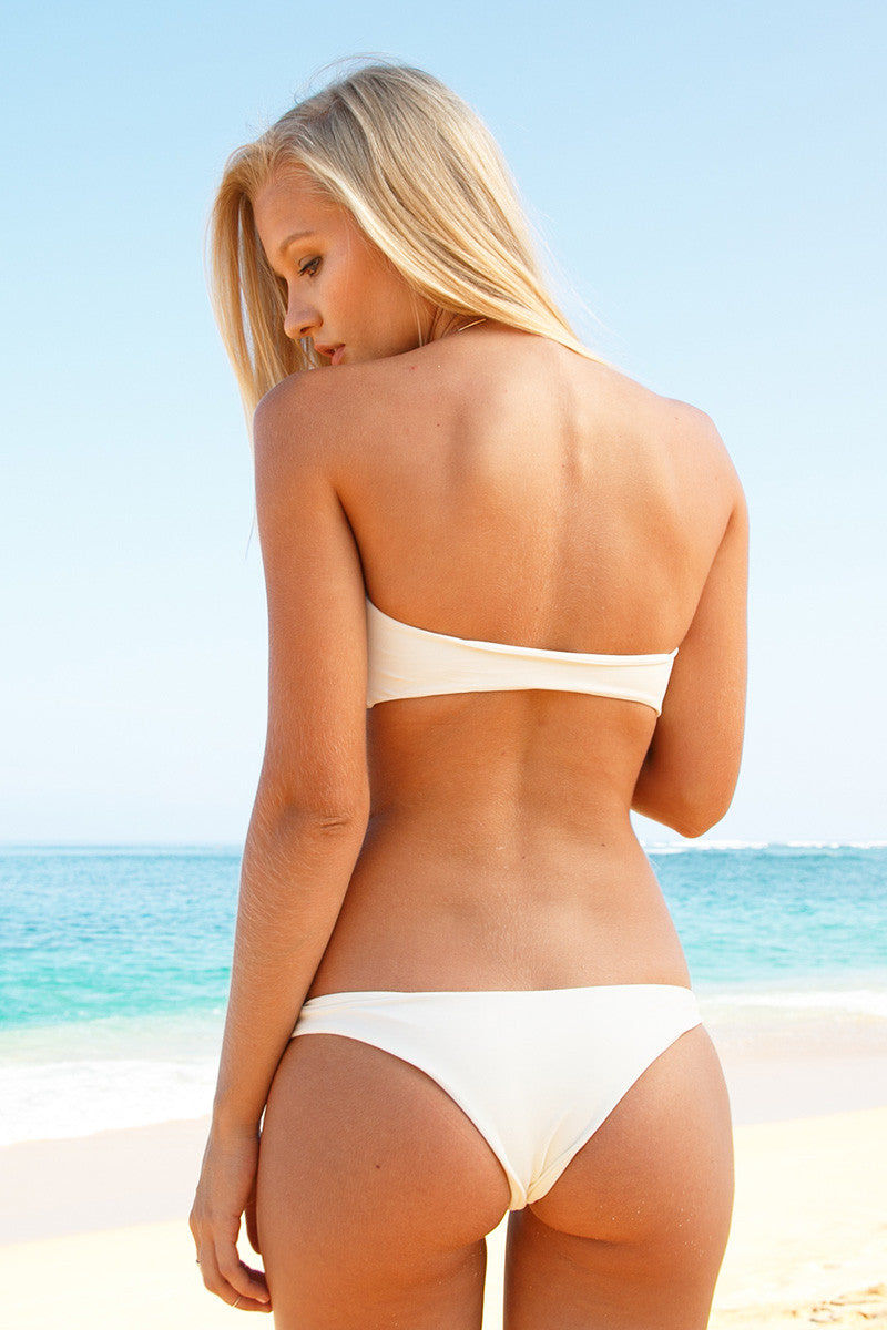MIKOH Lahaina Low Rise Seamless Bikini Bottom - Bone Bikini Bottom | Bone | Mikoh Lahaina Low Rise Seamless Bikini Bottom - Bone. Features: Low Rise skimpy minimalist bikini bottom. Wide side straps can be hiked up at the hips to create the appearance of elongated legs. Seamless and hardware-free. View: On model, full back view.