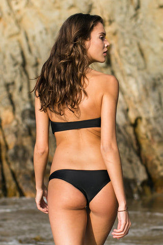 MIKOH Lahaina Low Rise Seamless Bikini Bottom - Night Bikini Bottom | Night|Mikoh Lahaina Low Rise Seamless Bikini Bottom - Night. Feature: Low rise skimpy minimalist bikini bottom. Wide side straps can be hiked up at the hips to create the appearance of elongated legs. Seamless and hardware-free. Double lined. View: On model, full back view.