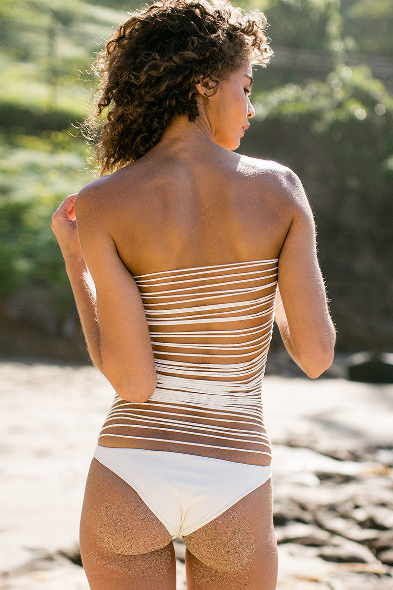 MIKOH Santorini Stringy Open Back One Piece Swimsuit - Bone One Piece | Bone| Mikoh Santorini Stringy Open Back One Piece Swimsuit - Bone. Features: String work open back. Solid front one piece. Light boning at sides of strapless top for support. Brazilian coverage. View: On model, full back view.