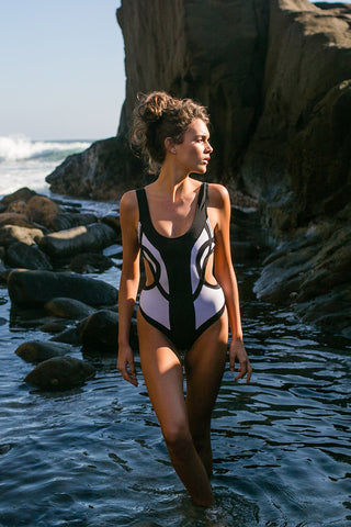 OYE SWIMWEAR Rorschach Cut Out One Piece Swimsuit - White & Black One Piece | White & Black| Oye Swimwear Rorschach Cut Out One Piece Swimsuit - White & Black. Features : Elegant Black and white cutout monokini one piece swimsuit. Named for the comic book character in the watchmen. Symmetrical color-blocked pattern looks like a one piece in front, but separates when seen from behind. Thick tank-top style straps and plunging scoop neckline with back clasp to secure fit and add an alluring silhouette. Fully lined. Suitable for D and DD cup sizes. Can be worn as a bodysuit.