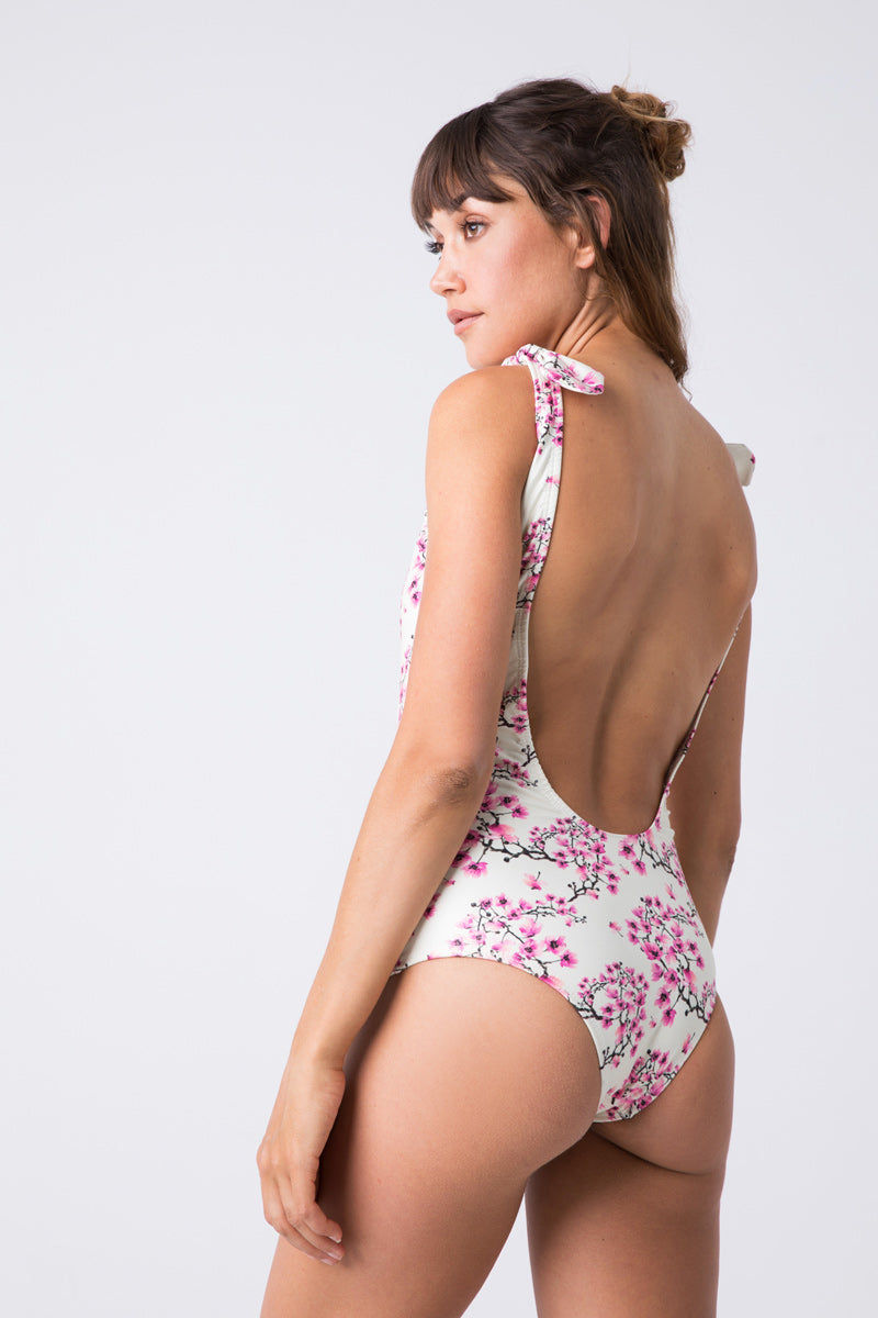 VERDELIMON Osaka Shoulder Ties One Piece Swimsuit - Nude Blossom One Piece | Nude Blossom| Verdelimon Osaka Shoulder Ties One Piece - Nude Blossom Scoop neckline one piece swimsuit. Bow detail at top of each shoulder strap. Cream fabric offset by a pink cherry blossom print. Super-low scoop back. Moderate coverage.