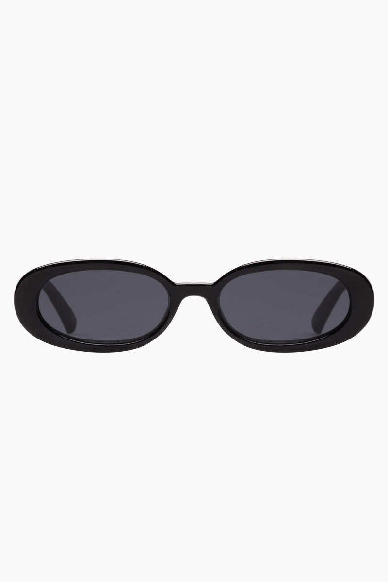 LE SPECS Outta Love Sunglasses - Black Sunglasses | Black| Outta Love - Le Specs Oval Sunglasses Modern Flat Profile  Flagstripe metal hardware  Frame:  Black Lens: Smoke Mono  Good UV protection Gender: Women Lens Width - Nose Bridge - Temple Length      51                   17                    140