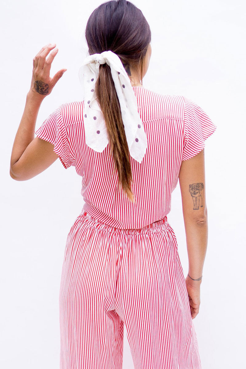 XIX PALMS Puerto Rico Short Sleeve Front Knot Crop Top - Red & White Stripe Print Top | Red & White Stripe Print | XIX Palms Puerto Rico Short Sleeve Front Knot Crop Top - Red & White Stripe Print Deep V-neck flutter short sleeve crop top in red and white stripe print. The seductive deep V-neckline Adorable flutter-style short sleeves  Adjustable front knot tie Back View