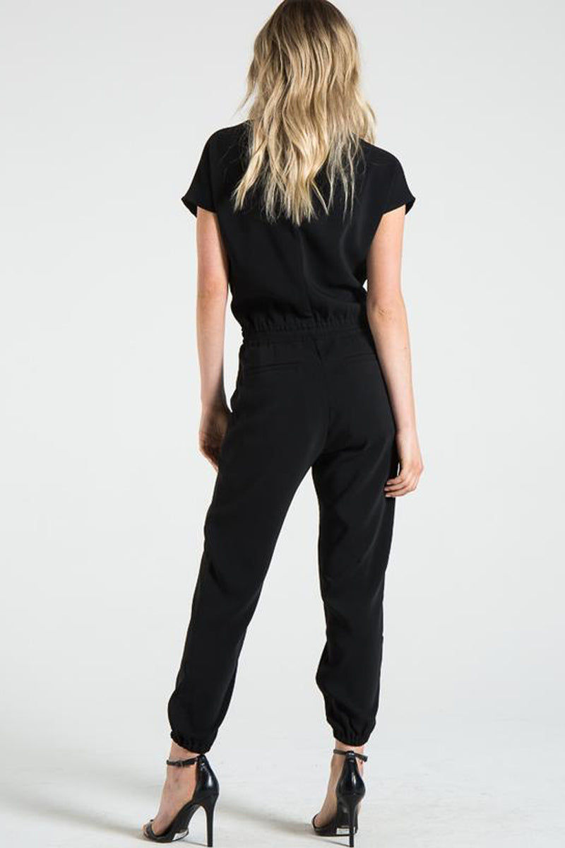 N:PHILANTHROPY Pierce Jumpsuit - Black Cat Jumpsuit | Black Cat| N:PHILANTHROPY Pierce Jumpsuit - Black Cat. Features:  Relaxed fitting v neck jumpsuit Key and button closure at back Side pockets Elastic waist with welt pocket details on back Elastic leg opening Cupro polyester spandex fabric Machine wash cold like colors, lay flat to dry Front View