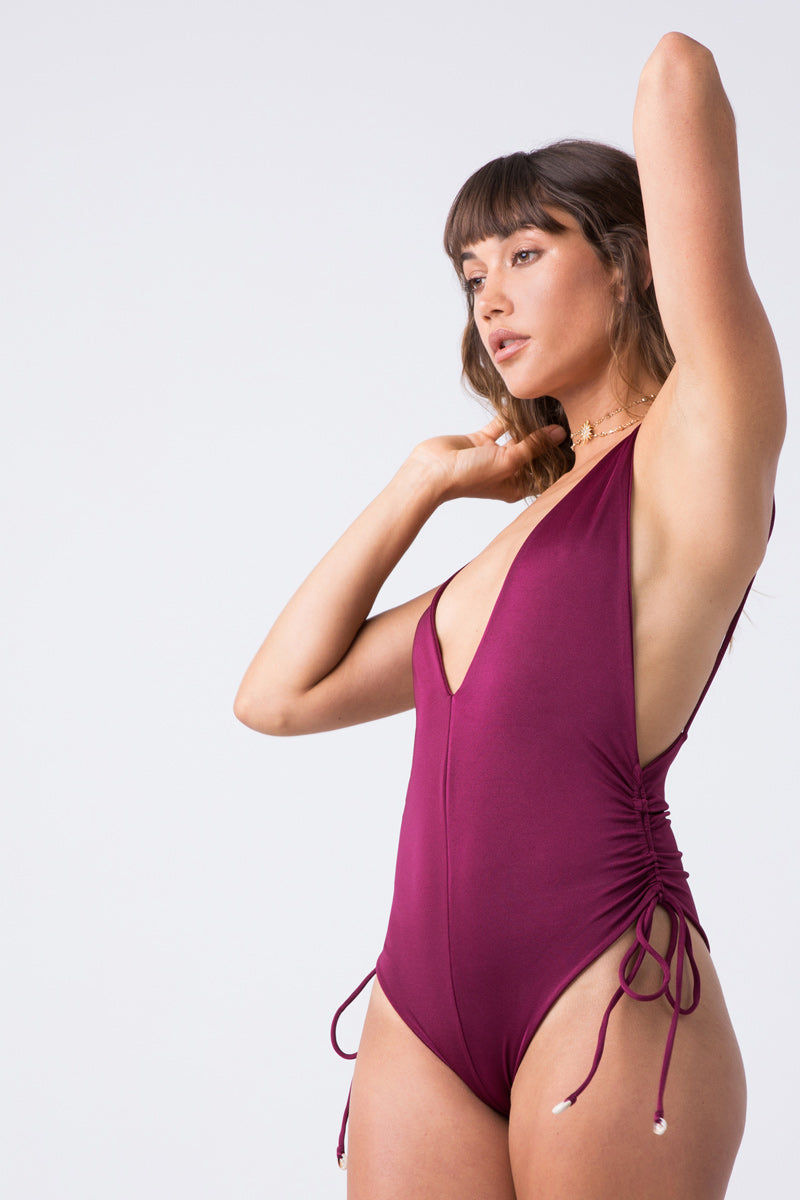 INDAH Playground Side Cinch One Piece - Bordeaux One Piece | Bordeaux| Indah Playground Side Cinch One Piece - Bordeaux Flatlay View Plunging V Neckline Spaghetti Straps Side Boob Exposure Cinched Sides Low Scoop Back High Cut Leg Thong Coverage Italian Shiny Lycra