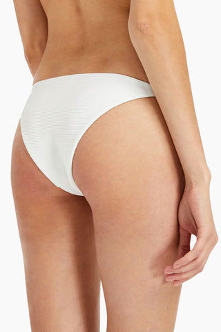 ONIA Rochelle Thin Side Strap Bikini Bottom - White Bikini Bottom | White| Onia Rochelle Thin Side Strap Bikini Bottom - White. Features: Cheeky low-rise bikini bottom in sophisticated white ribbed fabric. High-cut legs with strappy stretch sides make the minimal coverage bikini bottom ideal for tanning. View:  On model, up close back view.