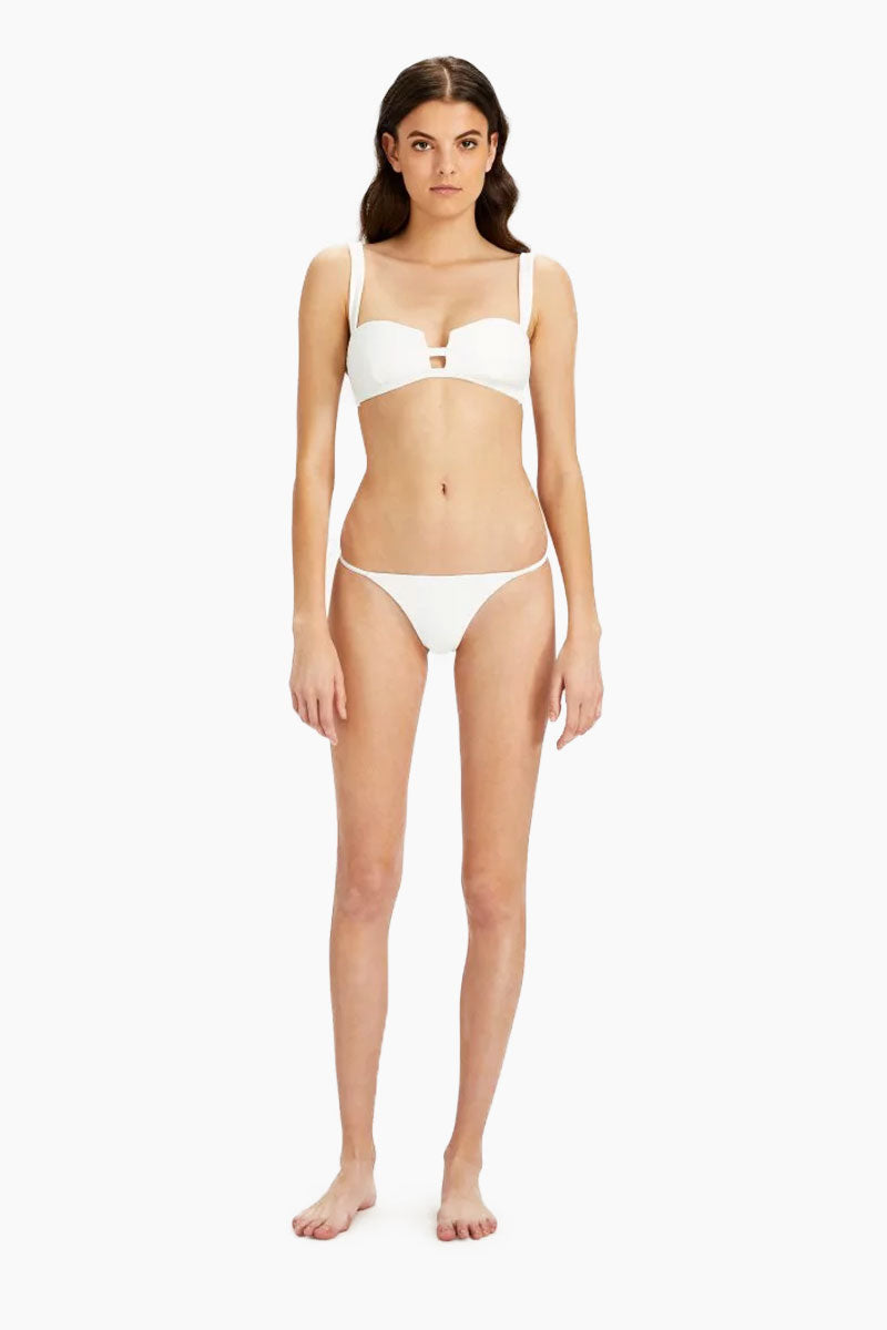 ONIA Rochelle Thin Side Strap Bikini Bottom - White Bikini Bottom | White| Onia Rochelle Thin Side Strap Bikini Bottom - White. Features: Cheeky low-rise bikini bottom in sophisticated white ribbed fabric. High-cut legs with strappy stretch sides make the minimal coverage bikini bottom ideal for tanning. View:  On model,  front view