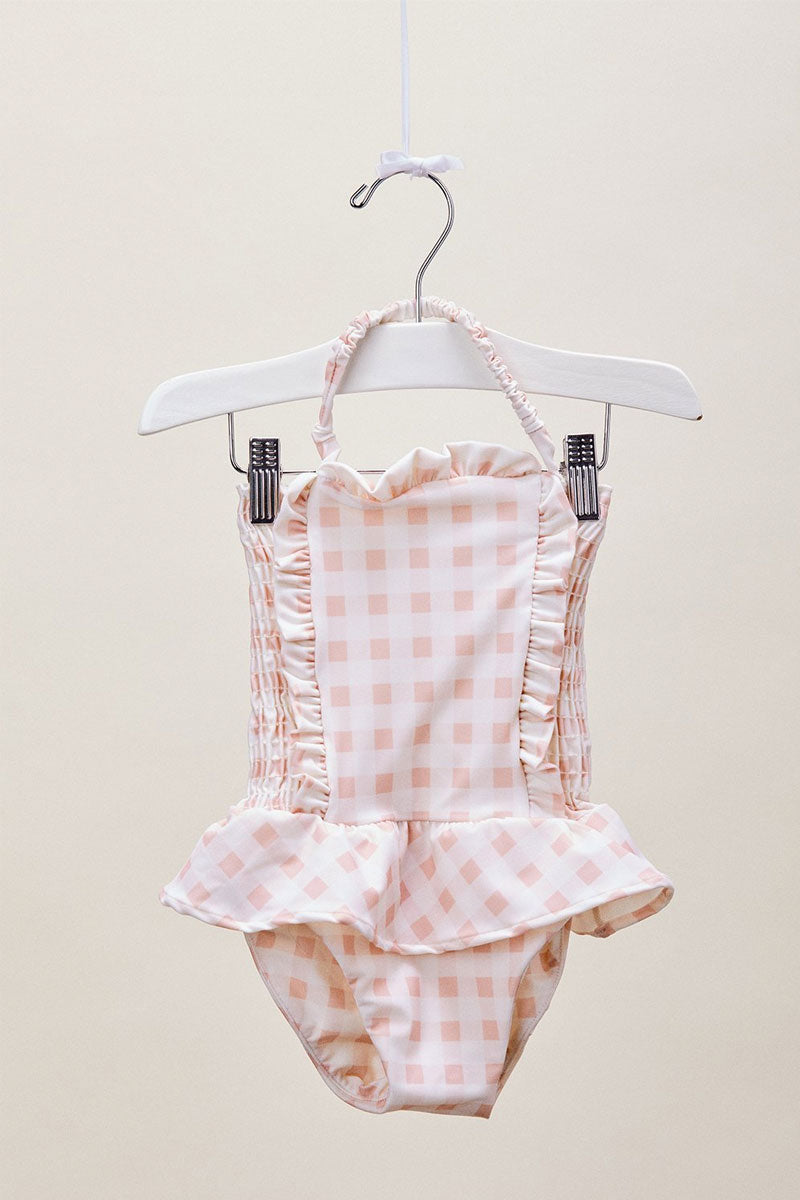 LIL LEMONS Ruffle Swim One Piece (Kids) - Pink Gingham Kids One Piece |  Pink Gingham| LIL LEMONS Ruffle Swim One Piece (Kids) - Pink Gingham. Features: •	Cute gingham print •	Ruffle detailing throughout •	Playful ruffled skirt •	Adjustable halter straps Front View