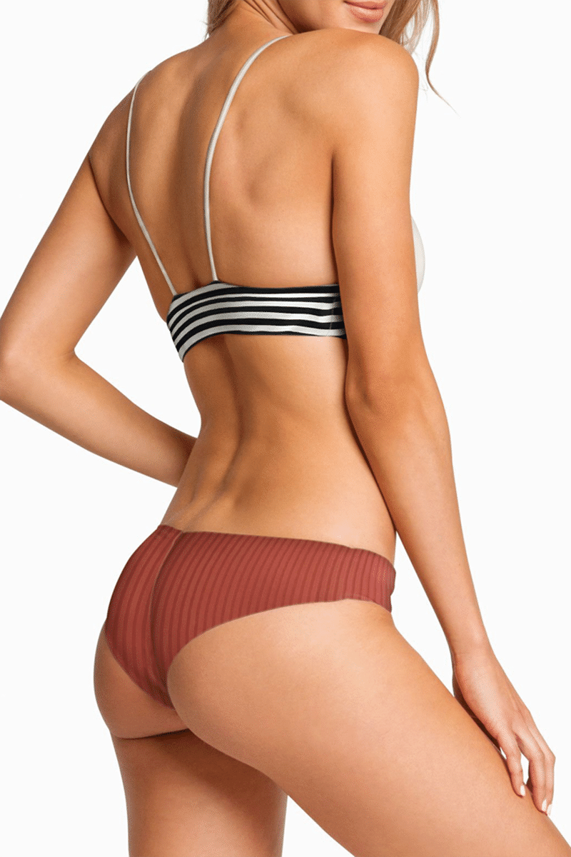 BOYS + ARROWS Kiki Ribbed Cheeky Ruched Bikini Bottom - Brick Haus Red Bikini Bottom   Brick Haus Red  Boys + Arrows Kiki Ribbed Cheeky Ruched Bikini Bottom - Brick Haus Mid Rise moderate coverage bikini bottom with ruched seam at rear. On-trend ribbed brick red fabric. Wide side straps provide an ultra-comfortable fit that never digs in. Ruched center seam at back Back View