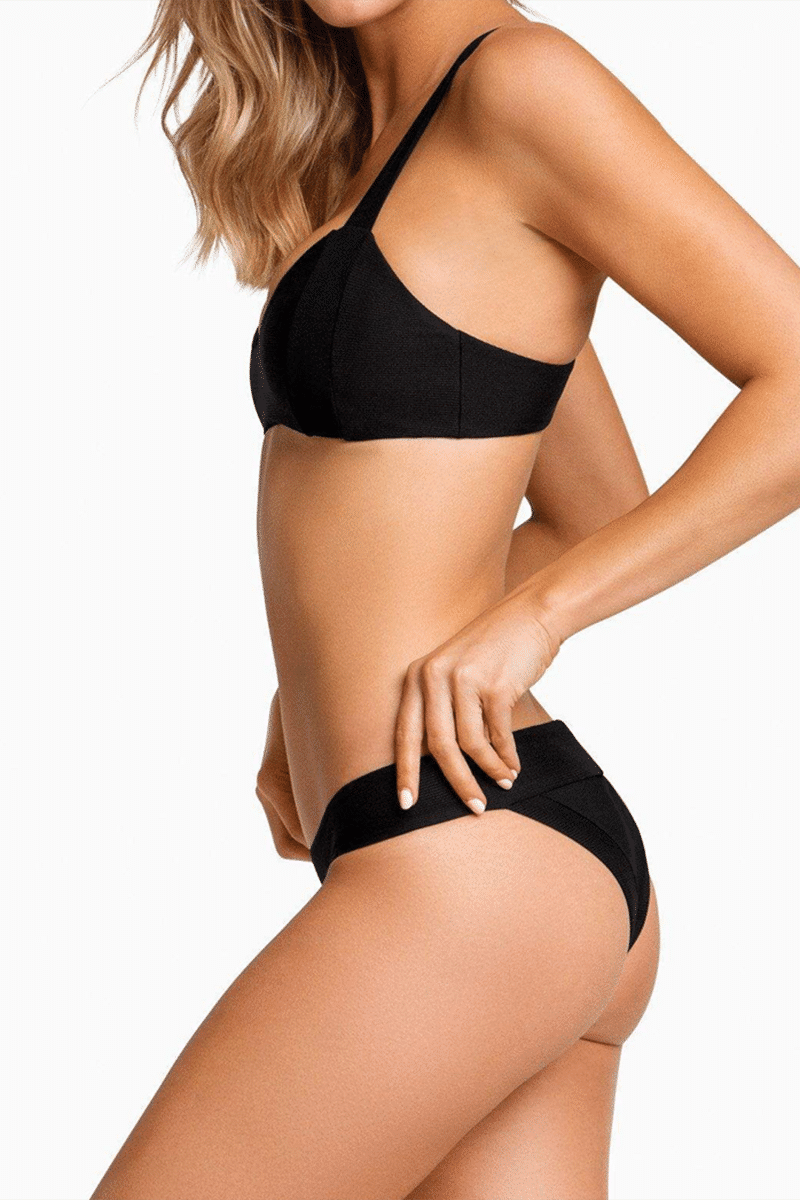 BOYS + ARROWS Scout Low Rise Skimpy Bikini Bottom - Black Bikini Bottom | Black| Boys + Arrows Scout Low Rise Skimpy Bikini Bottom - Black Low-rise skimpy banded bikini bottom in black. Seamless sides offer a luxurious feel while keeping your hips looking smooth. Wide waistband with micro-ribbed texture provides ultimate comfort and will keep you secure and slippage-free while swimming. Easy pull-on style in stretch fit fabric perfect for laid-back beach days. Cheeky rear cut shows off your curves while providing skimpy coverage. Side View