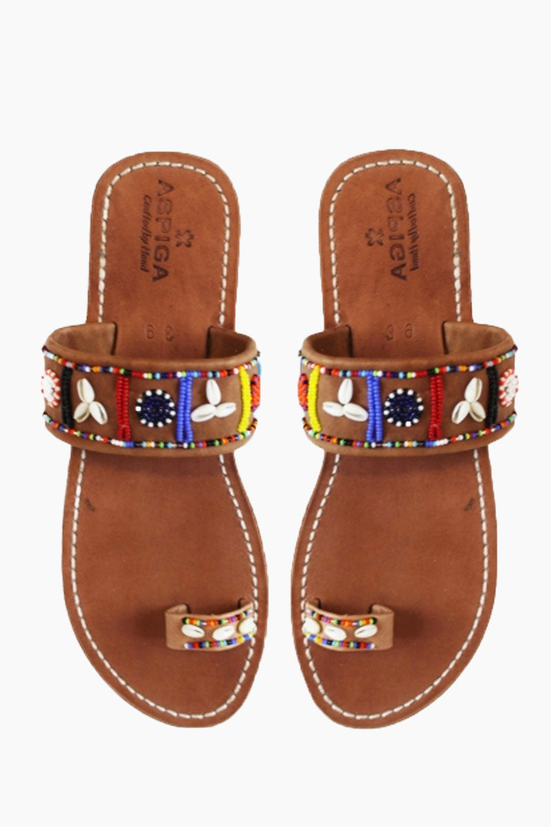 ASPIGA Shella Sandals - Multicolor Sandals | Multicolor| Aspiga Shella Sandals - Multicolor Toe loop style Over the foot strap with vibrant beadwork Flat flexible rubber sole Genuine tan leather upper Contrast white stitching Hand crafted in Kenya Front View
