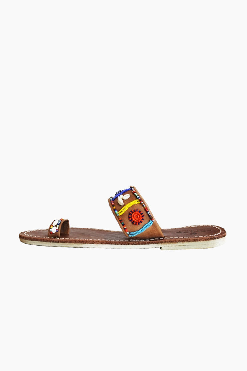 ASPIGA Shella Sandals - Multicolor Sandals | Multicolor| Aspiga Shella Sandals - Multicolor Toe loop style Over the foot strap with vibrant beadwork Flat flexible rubber sole Genuine tan leather upper Contrast white stitching Hand crafted in Kenya Side View