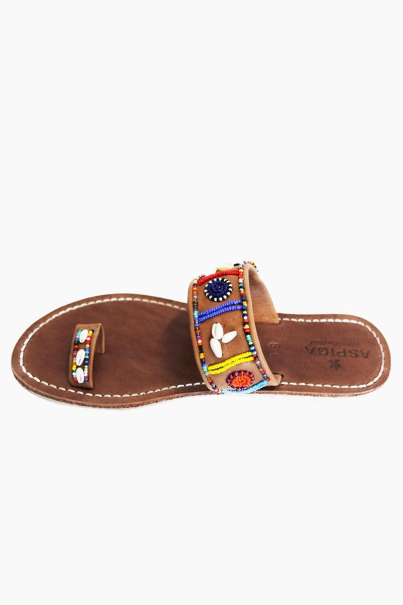 ASPIGA Shella Sandals - Multicolor Sandals | Multicolor| Aspiga Shella Sandals - Multicolor Toe loop style Over the foot strap with vibrant beadwork Flat flexible rubber sole Genuine tan leather upper Contrast white stitching Hand crafted in Kenya Top View