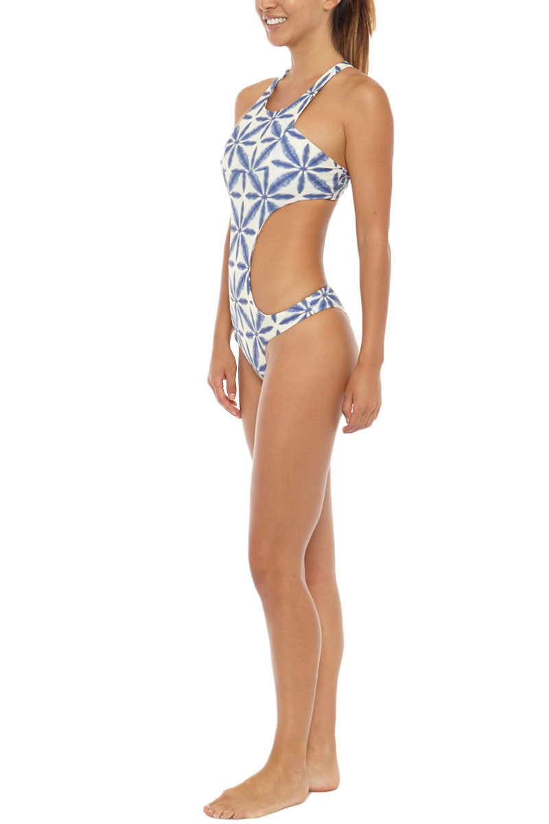 STONE FOX SWIM La Jolla Sporty Monokini One Piece Swimsuit - Ocean Blue Batik Print One Piece   Ocean Blue Batik Print  Stone Fox Swim La Jolla Sporty Monokini One Piece Swimsuit - Ocean Blue Batik Print Large cut-outs at sides continue to the back to create a monokini silhouette, giving you the best of both a bikini cut and a one-piece swimsuit. Ultra-flattering, athletic high neckline with wide shoulder straps frames your shoulders and arms. Racerback cut exposes skin at the center of the back through a small cut-out. Moderate rear cut shows off your curves while providing cheeky coverage. Side View