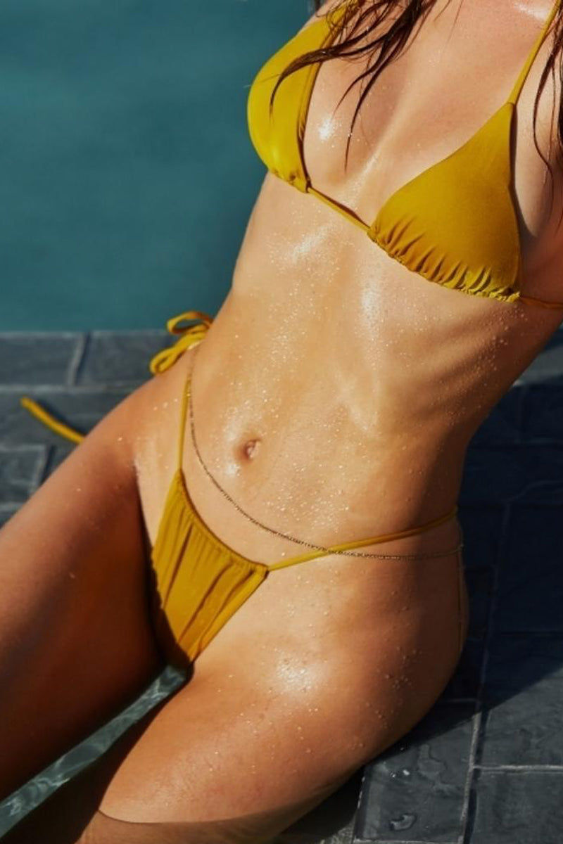 MONICA HANSEN BEACHWEAR That 90's Vibe String Bikini Bottom - Gold Bikini Bottom | Gold| Monica Hansen That 90's Vibe String Bikini Bottom - Gold Single tie side bikini bottom Thin string sides High cut leg  Adjustable coverage in front and back Skimpy to cheeky coverage