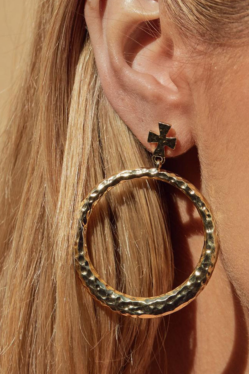 "LUV AJ The Hammered Cross Hoops - Gold Jewelry | Gold| Luv Aj The Hammered Cross Hoops - Gold. Features:  Pair of statement hoops with hammered texture and cross stud Posts are made from surgical steel so they are very hypo-allergenic Hoops are Approx. 3"" Tall Made from Brass Plated in Gold Front View"