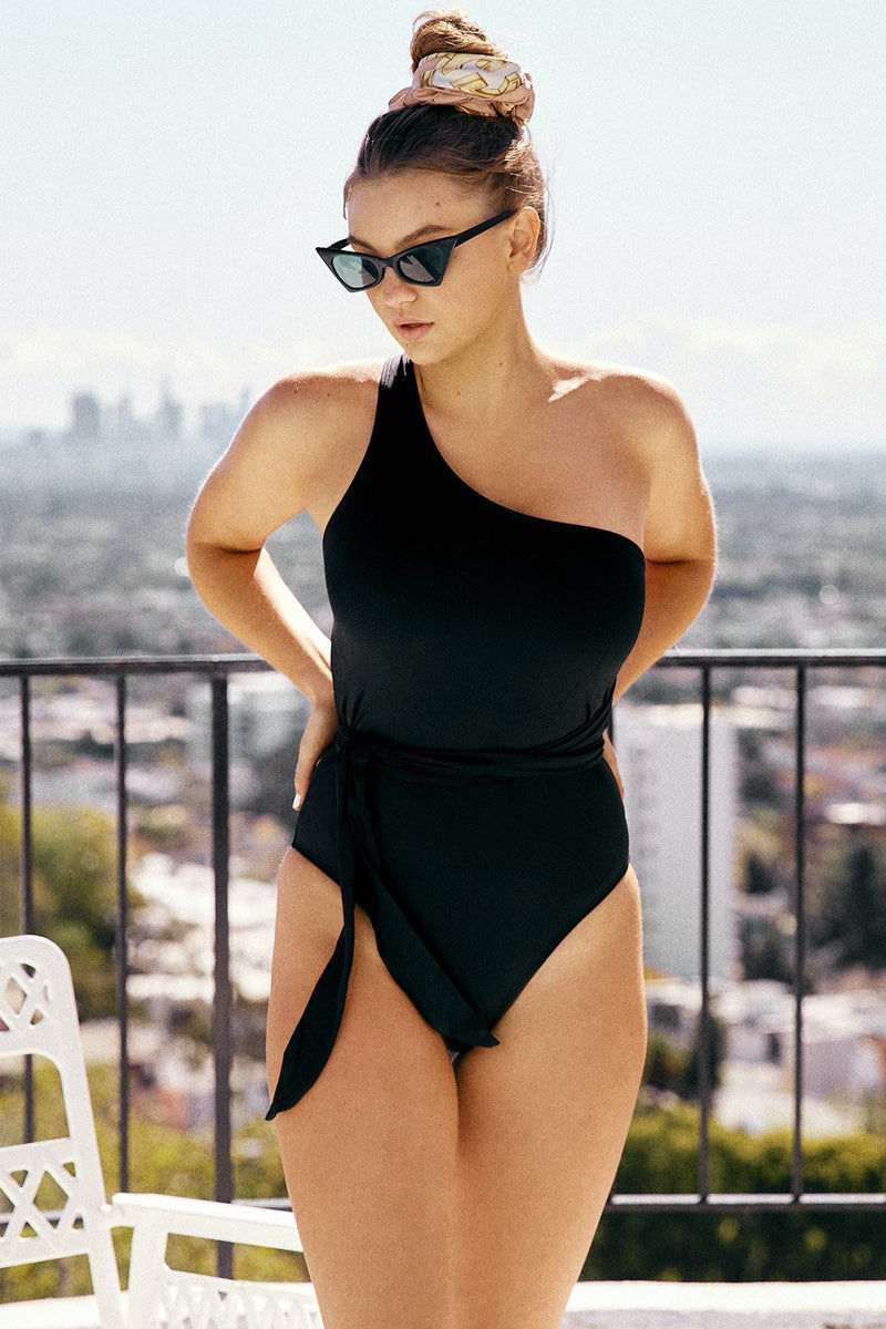 WE ARE HAH 1 4 Ur Soul One Shoulder One Piece Swimsuit - Noir Black One Piece | Noir Black| We are HAH 1 4 Ur Soul One Shoulder One Piece Swimsuit - Noir Black Strappy high-cut one shoulder one piece swimsuit in sleek solid black fabric. Sash-like single shoulder strap wraps around back and ties at waist in an on-trend belted look. Classic back tie closure combines with the adjustable wrap-around sash to guarantee the perfect figure-flattering fit. High-cut leg Front View