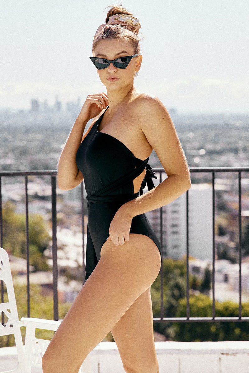 WE ARE HAH 1 4 Ur Soul One Shoulder One Piece Swimsuit - Noir Black One Piece | Noir Black| We are HAH 1 4 Ur Soul One Shoulder One Piece Swimsuit - Noir Black Strappy high-cut one shoulder one piece swimsuit in sleek solid black fabric. Sash-like single shoulder strap wraps around back and ties at waist in an on-trend belted look. Classic back tie closure combines with the adjustable wrap-around sash to guarantee the perfect figure-flattering fit. High-cut leg Side View