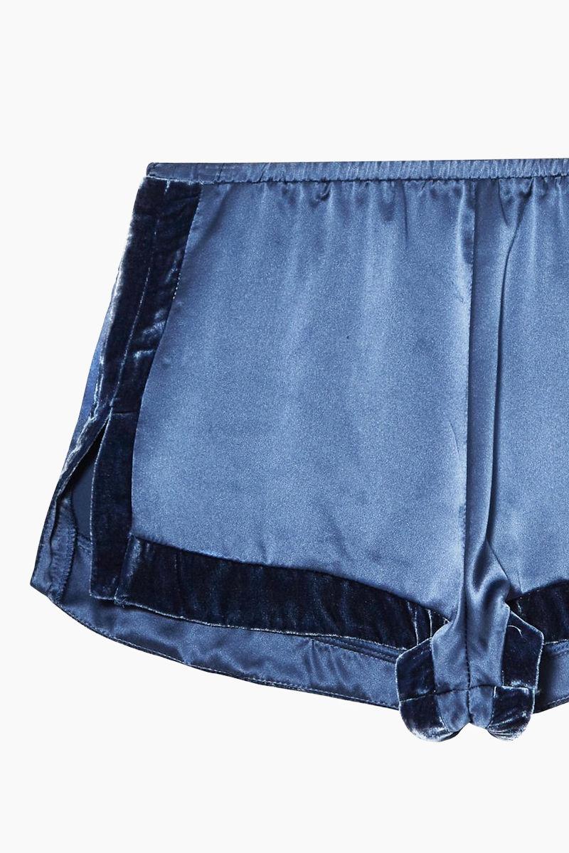 FLEUR DU MAL Velvet Trim Silk Tap Shorts - Caspian Blue/Black Shorts | Caspian Blue/Black| Fleur Du Mal Velvet Trim Tap Shorts - Caspian Blue Silk shorts  Velvet trim  Elastic waist  Mini side slits  Front View