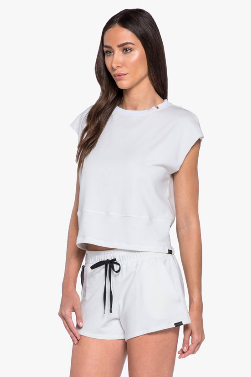 KORAL Watch Open Back Top - White Top | White| Koral Watch Open Back Top - White.  Features:  Open back top with strip trim detail.  Meant for Athleisure performance. Fabric: French Terry - 48% Modal, 47% Cotton, 5% Spandex  Machine wash cold, inside out with like colors; No bleach; Tumble dry low. inside out with like colors; No bleach; Tumble dry low. MADE IN USA Front View